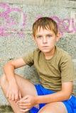 坐严肃的小男孩特写镜头画象户外 免版税库存图片