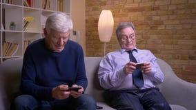 坐中的每一在自己的智能手机的资深男性朋友画象被吸收和感兴趣 股票视频