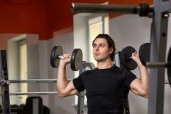 坐举重机器和举两个哑铃的黑sportwear的年轻肌肉被修造的运动员 免版税库存照片