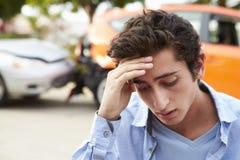 坐乘汽车的担心的少年司机在交通事故以后 库存照片