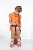 坐书和写在笔记本的女小学生 图库摄影