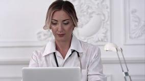 坐书桌和工作一台膝上型计算机的女性医生在医院 图库摄影