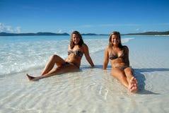 坐二个水年轻人的海滩女孩 免版税图库摄影