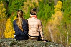 坐二的女孩岩石 库存图片