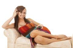 坐五颜六色的礼服边耳机的妇女听 免版税图库摄影