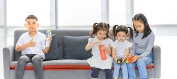 坐亚洲的孩子和拿着瓶在手上 免版税库存图片
