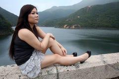 坐亚裔的女孩户外 免版税库存图片