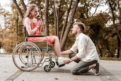 坐他的腰臀部分和接触心爱的妇女的腿的有同情心的人 库存图片