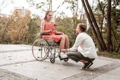 坐他的腰臀部分和看轮椅的年轻人女朋友 图库摄影