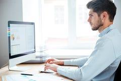 坐使用个人计算机的商人侧视图在办公室 库存照片