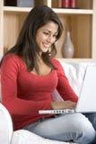 坐使用妇女年轻人的家庭膝上型计算&# 免版税库存照片
