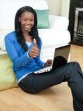 坐使用妇女的楼层愉快的膝上型计算&# 免版税库存图片