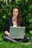 坐使用妇女年轻人的膝上型计算机公&# 免版税图库摄影