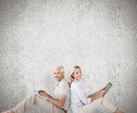 坐使用膝上型计算机和片剂个人计算机的愉快的夫妇的综合图象 库存照片