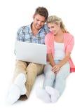 坐使用膝上型计算机的有吸引力的年轻夫妇 免版税库存图片