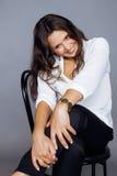 坐俏丽的深色的确信的成熟的妇女  图库摄影