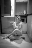 坐其次开放refriger的困妇女黑白照片 库存图片