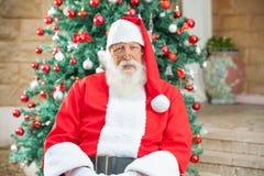 坐反对圣诞树的圣诞老人 图库摄影