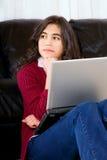 坐反对有膝上型计算机的长沙发的两种人种的青少年的女孩 库存照片