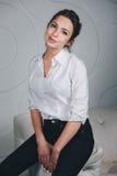 坐反对白色的年轻美丽的妇女 免版税图库摄影