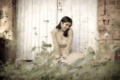 坐反对白色门的年轻美丽的印地安妇女在庭院里 免版税图库摄影