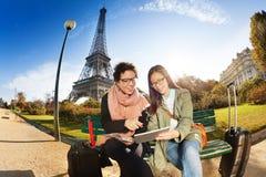 坐反对艾菲尔铁塔的两个游人 免版税库存照片