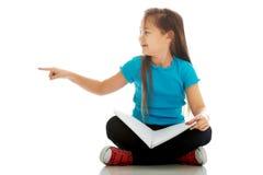 坐发怒有腿和学会的小女孩 免版税库存照片