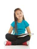 坐发怒有腿和学会的小女孩 免版税库存图片