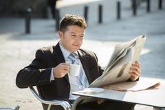 坐可爱的商人户外有早餐清早读书看起来报纸的新闻的咖啡杯放松 库存照片