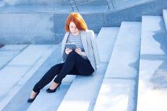 坐可爱的妇女读片剂和户外 免版税库存照片