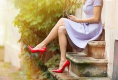 坐台阶和使用手机的妇女 免版税库存照片