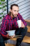 坐台阶和吃亚洲食物的方格的衬衣的人 免版税图库摄影