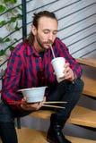 坐台阶和吃亚洲食物的方格的衬衣的人 图库摄影