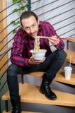 坐台阶和吃亚洲食物的方格的衬衣的人 免版税库存照片