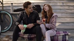 坐台阶和吃新月形面包,饮用的咖啡的一对美好的爱恋的夫妇的画象户外,坐  影视素材