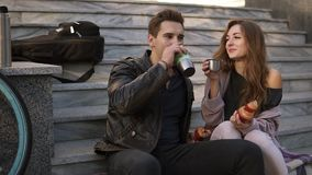 坐台阶和吃新月形面包,饮用的咖啡的年轻夫妇户外,坐格子花呢披肩和谈 股票视频