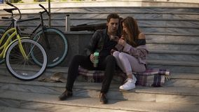 坐台阶和吃新月形面包,饮用的咖啡的美好的爱恋的夫妇户外,坐格子花呢披肩 股票视频