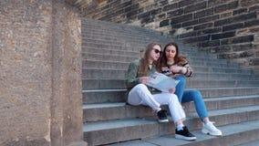 坐台阶和看地图的两个年轻女人旅客 影视素材
