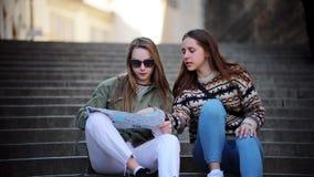 坐台阶和看地图的两名年轻旅行的妇女 股票视频