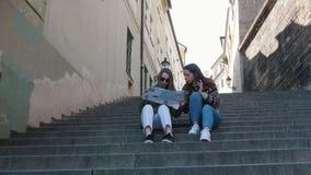 坐台阶和看地图的两年轻女人 谈话和谈论何处其次去 股票视频