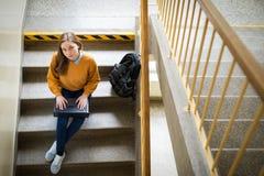 坐台阶在学校,写杂文在她的膝上型计算机和看照相机的年轻女性大学生 教育 免版税库存图片