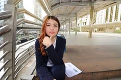 坐台阶方式和看在照相机的可爱的年轻亚裔女实业家画象在都市大厦背景中 免版税图库摄影