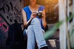 坐台阶,拿着葡萄酒照相机和看对照片的少妇做在城市游览 免版税库存图片