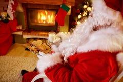 坐和享用在曲奇饼和牛奶的圣诞老人 免版税库存照片