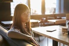 坐和作梦在咖啡馆的女孩 图库摄影