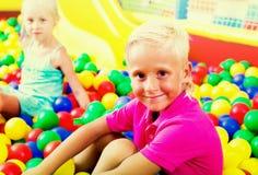 坐和使用与多彩多姿的塑料球的男孩 库存照片
