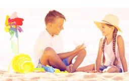 坐和使用与明亮的塑料玩具的孩子 库存照片