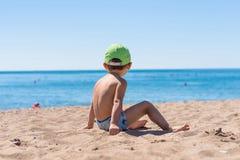 坐和使用与沙子的小男婴 免版税库存照片