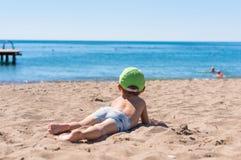 坐和使用与沙子的小男婴 库存照片