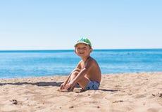 坐和使用与沙子的微笑的小男婴 免版税库存图片